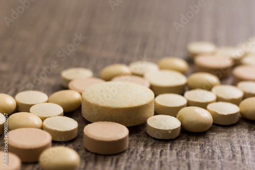 Heap of assorted beige capsules on wooden table.