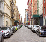 New York City cobblestone street scene with buildings and cars in the historic SoHo neighborhood of Manhattan - 190031709
