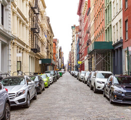 New York City cobblestone street scene with buildings and cars in the historic SoHo neighborhood of Manhattan