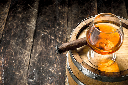glass of cognac with a cigar on a barrel.