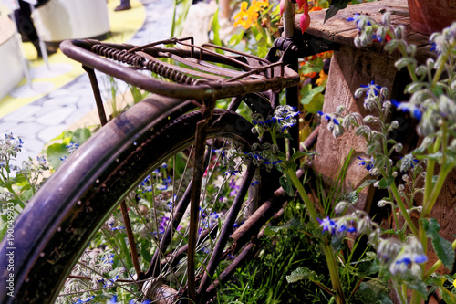 Fotobehang Fiets Old rusty and no longer functional fencing wheel in a garden with flowering flowers