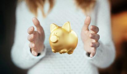 Mani con porcellino salvadanaio dorato, protezione economica