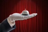 Hand in white glove is holding service bell. Red curtain in background. - 190065781