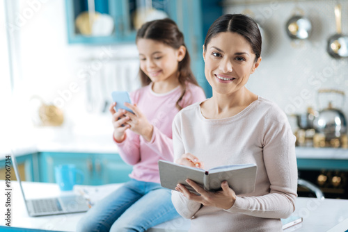 Happy mother. Attractive cheerful dark-haired woman smiling and holding and writing in the notebook while her daughter using her phone in the background