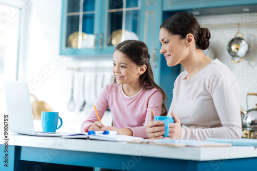 Learning lessons. Beautiful inspired dark-haired schoolgirl writing in her notebook and smiling while her mother standing near her with a cup