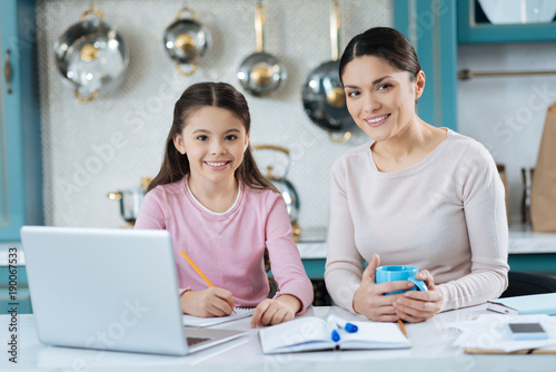 Feeling wonderful. Attractive alive dark-haired schoolgirl writing in her notebook and smiling while her mother standing near her with a cup