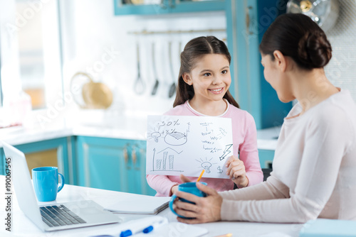 Explain please. Nice cheerful dark-eyed girl smiling and holding a sheet of paper and showing it to her mom standing near her