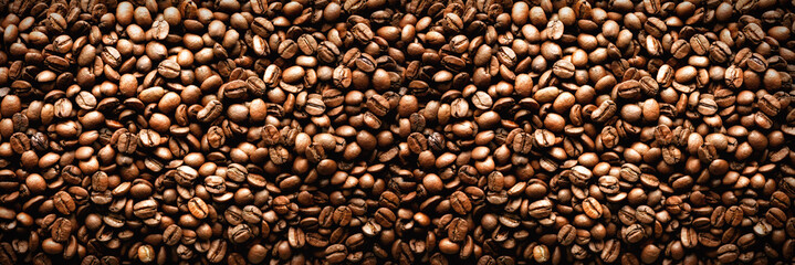 Roasted coffee beans backgound, copy space, top view. Cappuccino, dark espresso, aroma black caffeine drink, ingredient for coffee beverage. Banner © jchizhe