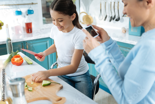 Happy moments. Pretty cheerful dark-haired girl smiling and chopping vegetable and making a salad while her mother taking pictures