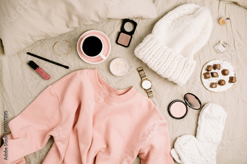 Female fashion look with stylish clothes and accessories. Beauty blog flat lay, top view composition with sweatshirt, cosmetics and coffee.