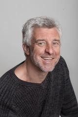 older gray-haired man sitting smiling
