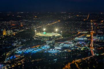 Melbourne Cricket Ground and Yarra Park tennis stadium illuminated at sunset.
