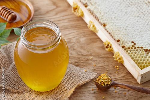 Aluminium Bee Honey jar, bee pollen and honeycombs on textured wooden table