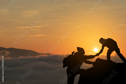 Two friends helping each other and with teamwork trying to reach the top of the mountains