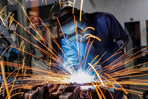 Industrial worker is welding car in factory