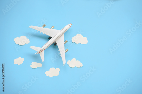 Foto Murales Flat lay design of travel concept with plane and cloud on blue background with copy space.