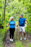Two older people trekking in the woods - 190100969