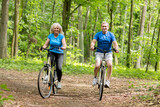 Two senior people cycling in the woods. - 190101150