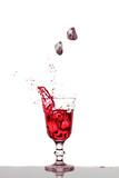 Eiswürfel fallen  in ein Glas mit rotem Getränk - 190107757