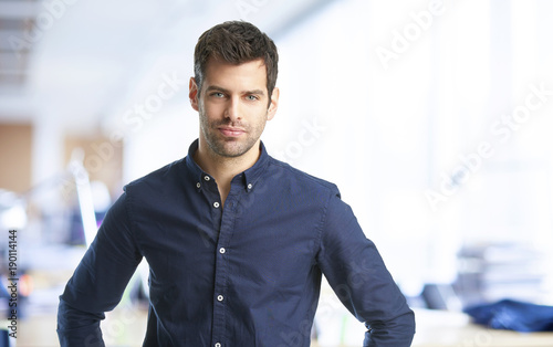 Young professional man. Confident young financial assistant businessman wearing shirt and looking at camera while standing at the office.
