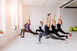 Group of women doing yoga, pilates and fitness and exercise indoors in white loft interior studio.