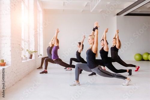 Plakat Group of women doing yoga, pilates and fitness and exercise indoors in white loft interior studio.