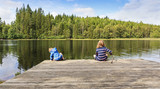 Two children using a homemade fishing rod fishing from a jetty by a lake set in an idyllic Swedish summer forest landscape. - 190114565