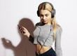 Beautiful blond  woman in headphones listening to music on white