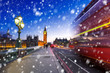 Big Ben and Westminster bridge on a cold winter night with falling snow, London, United Kingdom