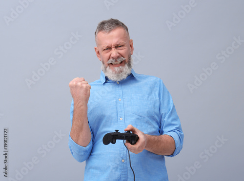 Happy senior man playing video game on grey background