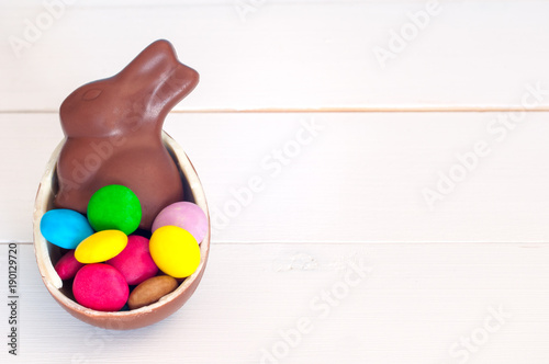 Close up view of chocolate bunny and chocolate candies on a white wooden background