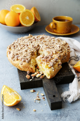 Orange pie with almonds. Gray wooden background