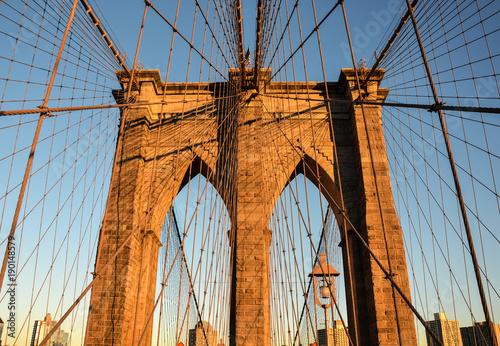 Fotobehang Brooklyn Bridge Atardecer reflejado en una de las majestuosas puertas del puente de Brooklyn, que une este distrito con la Isla de Manhattan en Nueva York