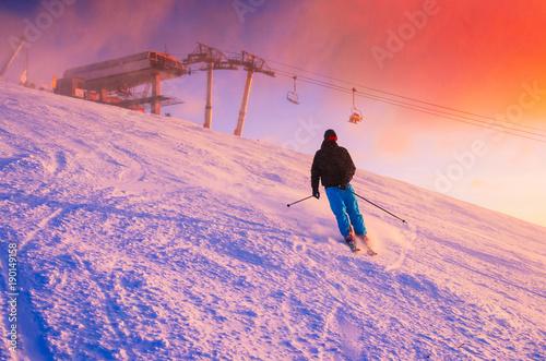 Foto op Aluminium Lichtroze Skier in ski resort. Red sunset sky in background.