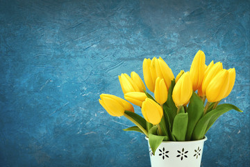 Yellow tulips bouquet in white vase. Decorative background, copy space