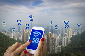 5G or LTE presentation. Woman hand using smartphone with modern city on the background