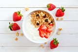 Bowl of yogurt with strawberries and granola, over a white wood background. Scattered berries.