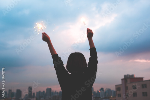 silhouette happy asia girl enjoy and play sparkler at rooftop party at evening sunset,Holiday celebration festive,teeage lifestyle,freedom and fun.