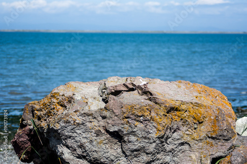 Tuinposter Blauwe jeans Mossy boulder with ocean behind