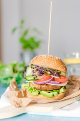 Tasty vegan burger with fresh vegetables on dark rustic wooden table, selective focus. Healthy fast food background with space for text.