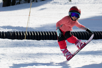 Little Cute Girl Snowboarding making a tricks at ski resort in sunny winter day. Caucasus Mountains. Mount Hood Meadows Oregon