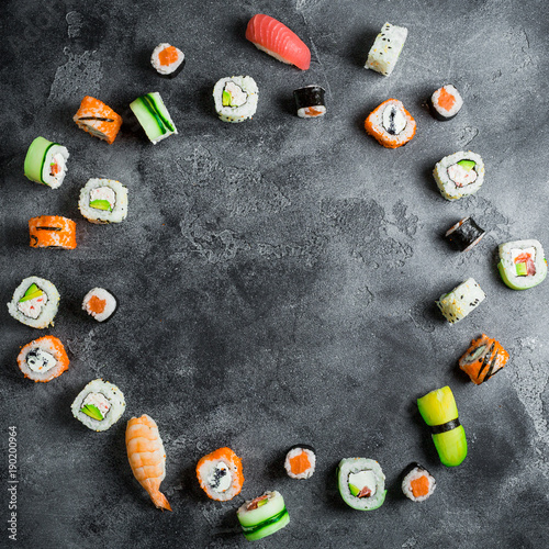 Keuken foto achterwand Sushi bar Round frame of set of Japanese food on dark background. Sushi rolls, nigiri, salmon steak, rice and avocado. Flat lay. Top view