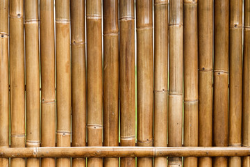 vertical yellow bamboo fence background close up