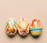 Three handmade Easter eggs on creamy background - 190205556
