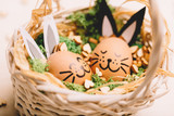 Two smiling egg-bunnies laying in the basket. - 190206376