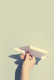Woman's hand playing with white paper plane - 190206387