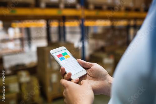 Fotobehang Hoogte schaal Man warehouse worker with a smartphone.