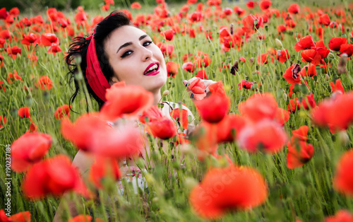 Young beautiful brunette woman with makeup in red head bandages in pin-up style sitting amongst poppies in a field. Outdoor portrait