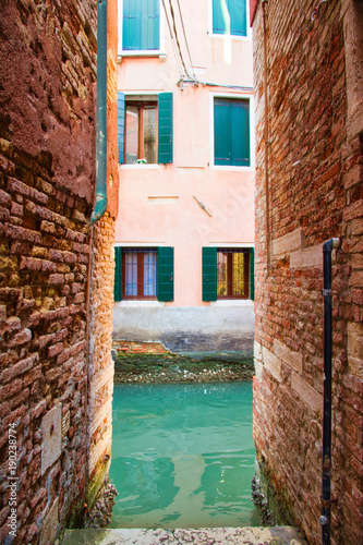 Foto op Canvas Smal steegje The end of a narrow alley in Venice leading to a canal with windows on the opposite side.