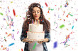 Teenage girl blowing candles on a birthday cake with confetti streamers flying around her